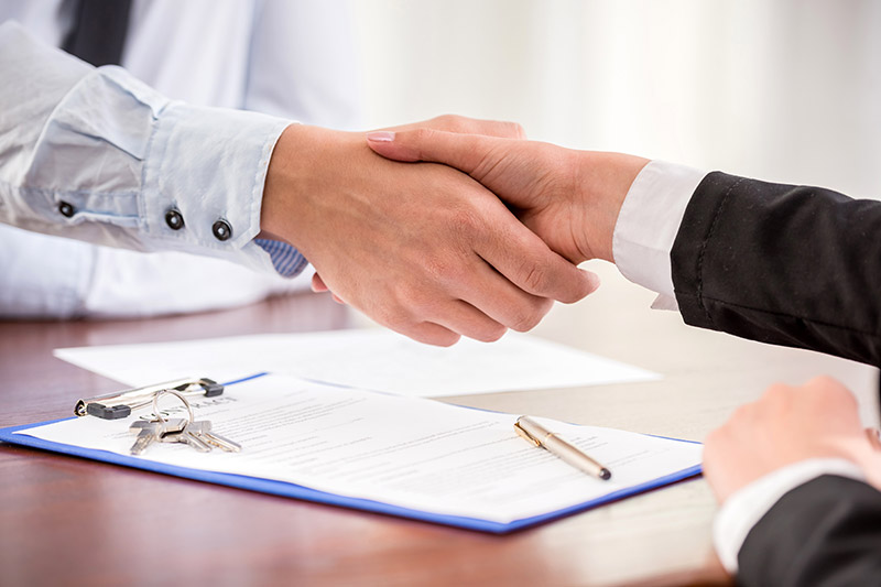 Men wearing suits shaking hands over a contract
