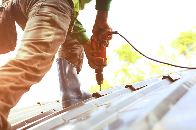Maintenance worker performing a repair on a roof